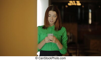 The young woman is standing working with the cellphone and then leaving the cafe hall.