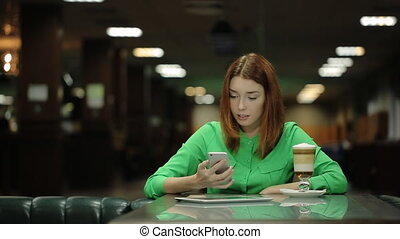 The young woman is staring to talk the cell phone sitting smiling at the table in the cafe.