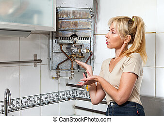 The young woman is upset by that the gas water heater has...