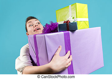 The young woman looks with joy and anticipation at the gifts