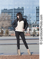 The young woman poses against the background of modern buildings.