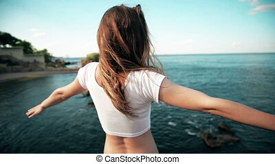 The young woman raised her hand up to the sun, against the sea, rocks and sky with clouds