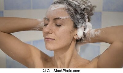 the Young woman taking a shower and washing hair with...