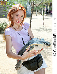 The young woman with a large turtle in hands