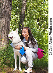 The young woman with a white dog on the nature