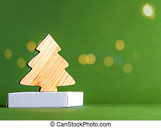 The zero waste new year concept as a wooden fir tree on the green background with the goldeb sparkles.
