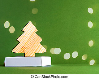 The zero waste new year concept as a wooden fir tree on the green background with the golden sparkles.