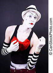 theatrical mime in white hat and striped gloves