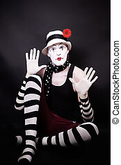 Theatrical mime with red flower sits on the floor