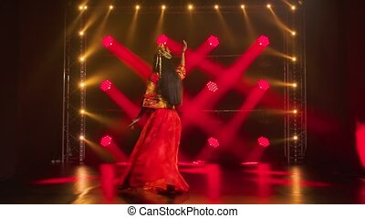 Theatrical performance of a beautiful woman dancer in red silk costume and headdress of a Chinese princess. Shot in a dark studio with red neon lights. Slow motion