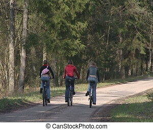 Thee cycling females traveling - Three cycling females...