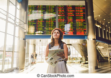theme travel and transportation. Beautiful young caucasian woman in dress and backpack standing inside train station terminal looking at electronic scoreboard holding phone, map paper hand navigation