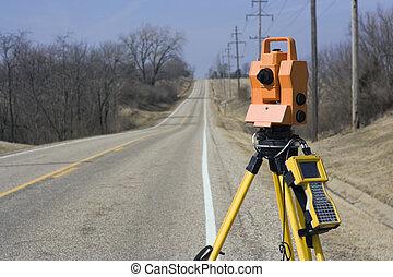 Theodolite set on the edge of road - spring land surveying.