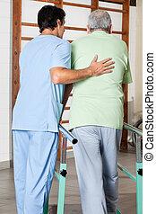 therapeut, assistieren, älterer mann, gehen, mit, der, unterstuetzung, von, stäbe