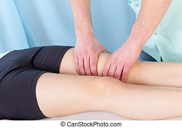 Therapeutic leg massage - Young female patient getting...