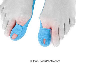 Therapeutic tape on female toe. - Therapeutic tape on female...