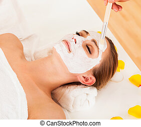 Therapist applying a face mask to the face of a beautiful...