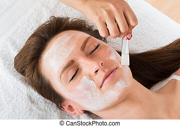 Therapist Applying Face Mask To Woman
