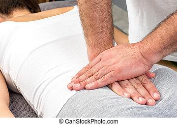 Therapist applying pressure on female tailbone.