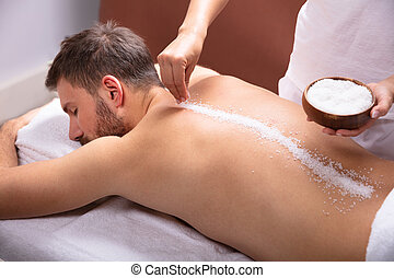 Therapist Applying Salt On Man's Back