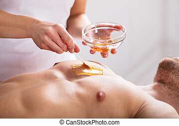 Therapist Applying Wax On Man's Body - Close-up Of A...