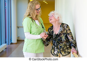 Therapist Assisting Elderly Walking In Hospital