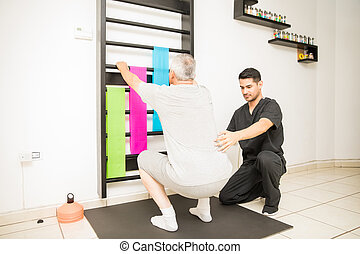 Therapist Assisting Mature Man Doing Squats In Clinic