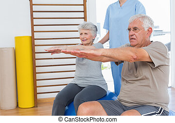 Therapist assisting senior couple with exercises