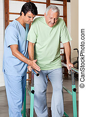 Physical therapist assisting senior man to walk with the support of bars at hospital gym