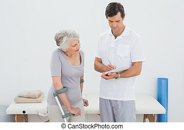 Therapist discussing reports with a disabled senior patient