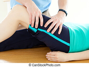 Therapist doing fitness exercises with a woman in gym