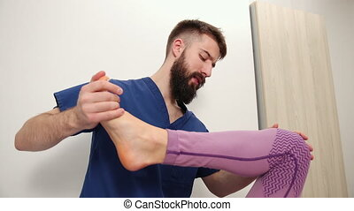 Therapist doing healing treatment on female leg, knee. Chiropractic, osteopathy, manual therapy. Alternative medicine, pain relief concept. Physiotherapist work with foot. Bearded man in hospital