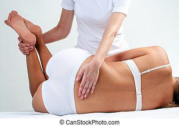 Therapist doing lower back massage on woman.