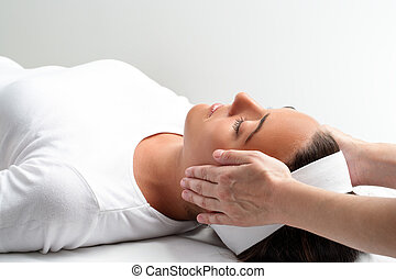 Therapist doing reiki with hands next to womans head. -...