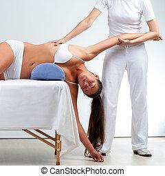 Therapist doing shoulder massage on woman.