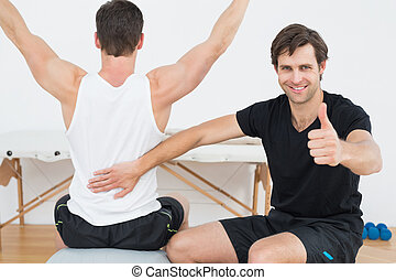 Therapist gestures thumbs up besides man on yoga ball