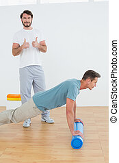 Portrait of physical therapist gesturing thumbs up with young man doing push ups in the gym at hospital