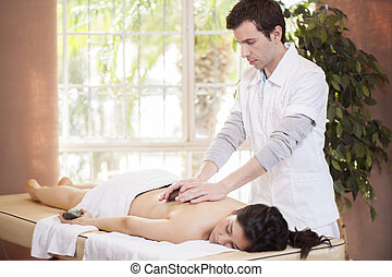 Therapist giving a stone massage
