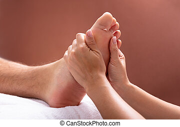 Therapist Giving Foot Massage To Man