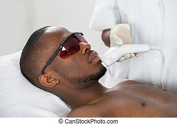 Therapist Giving Laser Epilation Treatment On Young Man -...