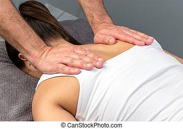 Therapist hands applying pressure on female shoulder blades.
