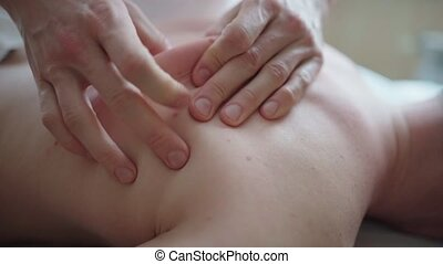 Therapist hands doing massage of mans back. Close-up slow...