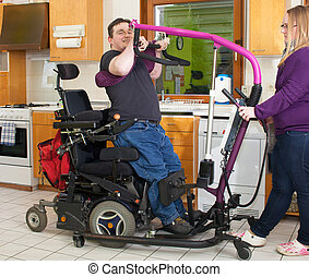 Therapist helping a spastic young man with infantile cerebral palsy caused by a complicated birth to maneuver himself into a multifunctional wheelchair with a patient lift