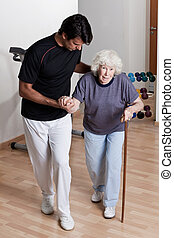 Therapist helping Patient To Walk - Therapist Helping...