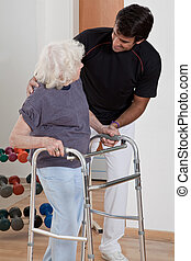 Therapist helping Patient use Walker - A therapist assisting...