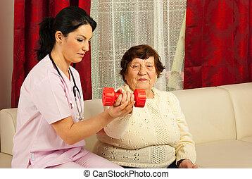 Therapist helping senior to do exercises - Therapist woman...