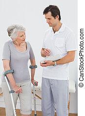 therapist, het bespreken, rapporten, met, een, invalide, senior, patiënt