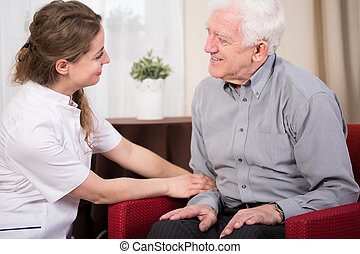 Therapist home visit - Young therapist during elderly...