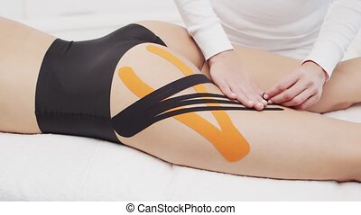Therapist is applying kinesio tape to female body. Physiotherapy, kinesiology and recovery treatment concepts.