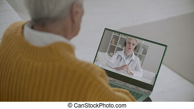 therapist is speaking about new coronavirus infection and preventive measures to old patient by video call, man is listing by laptop